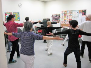 LINC class students and staff member doing tai chi in classroom