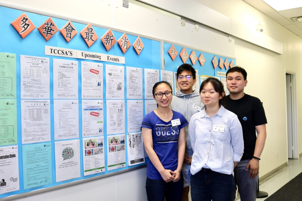 Volunteers standing in front of upcoming events bulletin board